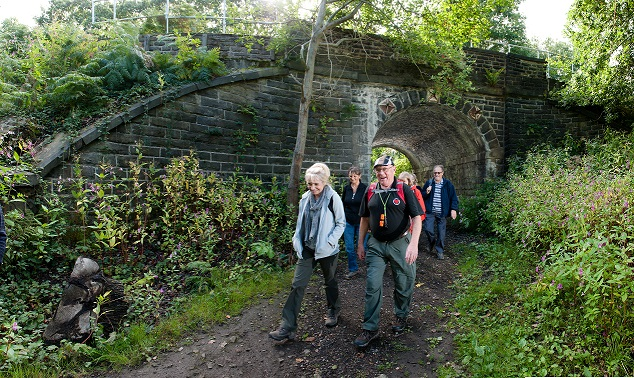 A CREW Walking session, comprising of 6 individuals walking underneath a bridge in the countryside near Halifax