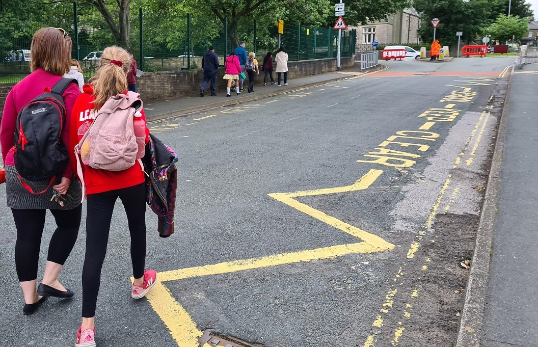 A family walk to school on a road closed to vehicles