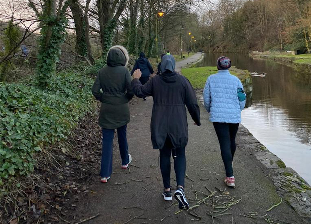 Showing the back of three ladies briskly walking on a path alongside a canal and another lady further in front. All three ladies are wearing coats, and trainers.