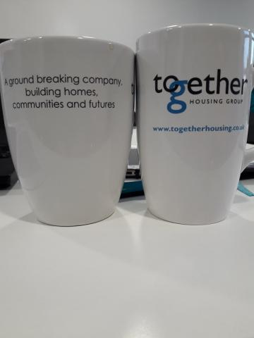 "A shot of two together housing mugs on a meeting table. One of the mugs has the together housing logo, the other reads ""a groundbreaking company, building homes, communities and futures"
