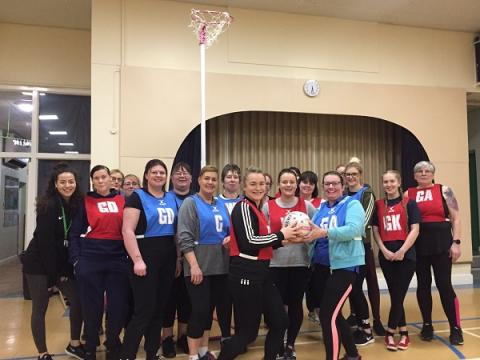 A group of around 20 ladies wearing netball bibs and posing with a netball at the front