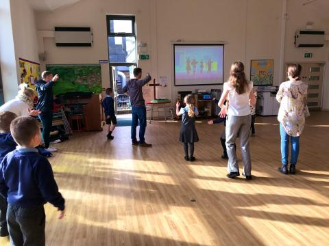 Children and their parents taking part in an activity in a school hall. They are following an interactive video on the smart board.