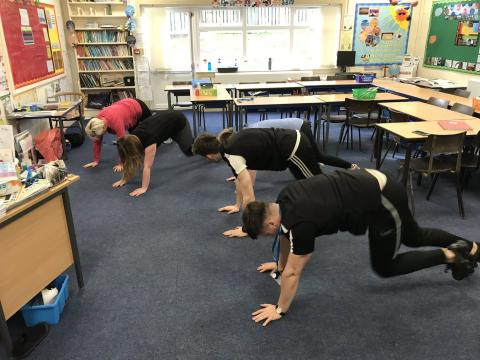 Five active teachers performing push ups in a class room. The tables have been pushed out of the way to make room.